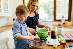 Mother and child preparing cookies in kitchen. Child helping mother make cookies as a professional chef royalty free stock image