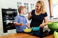 Mother and child preparing cookies in kitchen. Child helping mother make cookies as a professional chef royalty free stock images