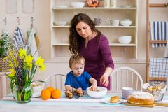 Child helping mother make cookies in modern kitchen. Mother and son cooking. Mother and son preparing dinner. Mother and baby near the table in the kitchen Royalty Free Stock Photo