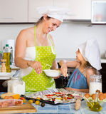 Child helping mother to make a pizza. Cute child helping mother to make a pizza Stock Photos