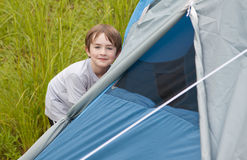 Child helping put up tent Royalty Free Stock Image
