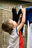 Child helping with washing. Child hanging laundry on a washing line Royalty Free Stock Photos