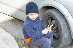 Child helps dismantle a car wheel stock photos