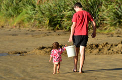 Child helps to carry a heavy bucket Royalty Free Stock Images