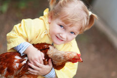 Child with hen. Baby girl in yellow holding hen Royalty Free Stock Images