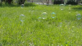A child with her mother is playing with soap bubbles. A happy family in the wild. Mom and daughter are blowing bubbles.