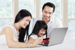 Child and her parents shopping online at home Stock Photo