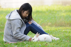 Child and Her Pet Bunny Playing Outdoors. In garden stock photo