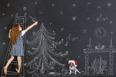 Child and her puppy decorates a Christmas tree drawing on blackb Royalty Free Stock Photography
