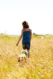 Child and her puppy walking in a field of grass stock photos