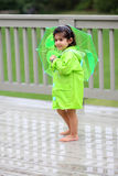 Child and her rain gears. Young girl playing in the rain with rain gears Royalty Free Stock Photography