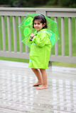 Child and her rain gears. Young girl playing in the rain with rain gears Royalty Free Stock Image