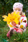 Child hidden behind autumn leaves Royalty Free Stock Images