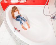 Child hiding in the bathroom, playing in tablet Stock Images