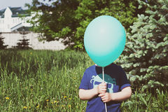 Child hiding behind the balloon Royalty Free Stock Photography
