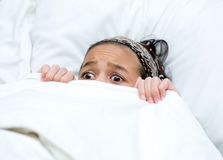 Child hiding behind blanket while watching movie Royalty Free Stock Images