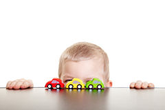 Child hiding behind toy cars. Little boy hiding behind three toy cars Stock Photos