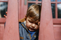 A child is hiding behind two wooden bars Royalty Free Stock Images
