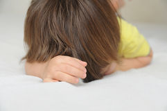 Child hiding face lying on bed, crying  offended little girl. Child hiding face lying on bed , crying  offended little girl Stock Photography