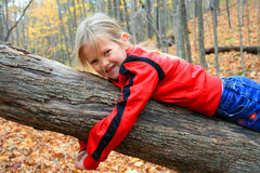 Child on hike. A little girl laying on a fallen tree trunk while on a field trip hiking in the woods with the autumn leaves all around her Stock Photo