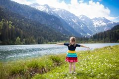 Child hiking in flower field at mountain lake stock images