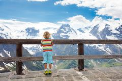 Child hiking in mountains. Kids in snow in spring. Children hiking in Alps mountains, Austria. Kids at snow covered mountain peak on warm sunny spring day royalty free stock photography
