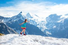 Child hiking in mountains. Kids in snow in spring. Children hiking in Alps mountains, Austria. Kids at snow covered mountain peak on warm sunny spring day stock image