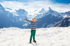 Child hiking in mountains. Kids in snow in spring. Children hiking in Alps mountains, Austria. Kids at snow covered mountain peak on warm sunny spring day stock photography
