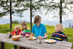 Child hiking in mountains. Picnic for kids stock photo