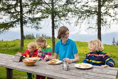 Child hiking in mountains. Picnic for kids. Child hiking in Alps mountains, Austria. Kids eating sandwich on picnic during hike at snow covered mountain peak on Stock Photos
