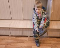 the child himself dresses in the changing rooms of the kindergarten. a little boy dresses his shoes himself. Child in the locker royalty free stock image