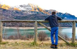 Child with his arms on a wooden fence observing the snow on the peaks of the mountains and the blue water of the lake in the royalty free stock images