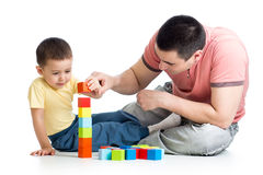 Child and his dad play with building blocks Stock Image