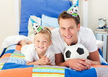 Child and his father playing with a soccer ball Royalty Free Stock Photos