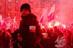Independence Day March in Warsaw Poland Marred by Violence and Controversy. A child on his fathers shoulders looks into the camera as flares are fired i n the Stock Photos