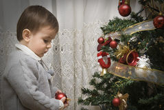 Child with his first Christmas tree. A little child impressed by his first time wdecorating the Chirstmas tree Stock Image