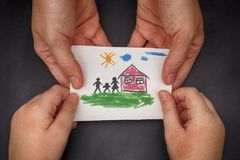 Child and his mom holding a drawn house with family Stock Images