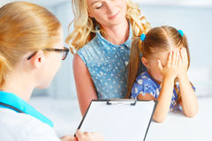 Child with his mother afraid of  visit to doctor Stock Photo