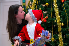 The child with his mother Christmas day. The child in a suit of the Christmas gnome with his mother on the background of Christmas tree. The child pulls kiss mum Royalty Free Stock Photography