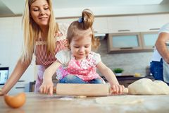 A child with his mother prepares the dough for cookies. A child with his mother prepares the dough for cookies in the kitchen stock photos