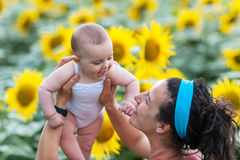 Child in his mother's arms in a field of sunflowers Royalty Free Stock Image