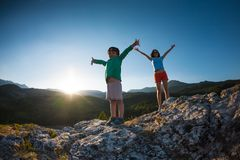 A child with his mother on top of a mountain. A child with his mother on top of a mountain at sunset. The boy enjoys climbing to the top. The women and her son stock photo
