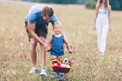 Child with his parents pushing a whellbarrow outdoors stock photography