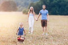Child with his parents pushing a whellbarrow outdoors. Adorable child with his parents pushing a whellbarrow outdoors stock photo