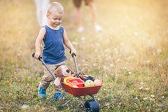 Child with his parents pushing a whellbarrow outdoors. Adorable child with his parents pushing a whellbarrow outdoors stock photos
