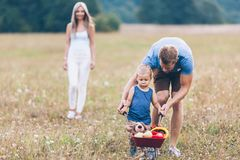 Child with his parents pushing a whellbarrow outdoors. Adorable child with his parents pushing a whellbarrow outdoors royalty free stock image