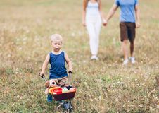 Child with his parents pushing a whellbarrow outdoors. Adorable child with his parents pushing a whellbarrow outdoors royalty free stock photography