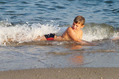 Child hit by a sea wave. Kid being hit by a sea wave in shallow water Stock Photo