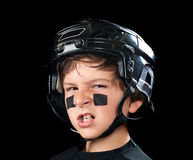 Child hockey player. A youth hockey player wearing protective headware snarls at the camera royalty free stock photo