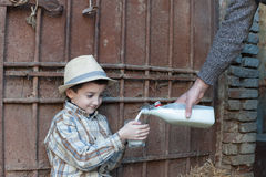 Child hold a glass of fresh milk. Child is holding and drinking a glass of fresh milk Stock Photos